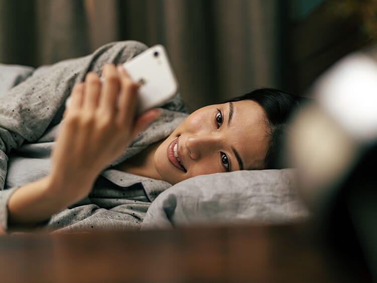 スマホを見ながら寝ている女性イメージ